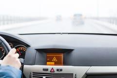 Advertencia resbaladiza del camino en la exhibición del coche, fuera del coche del foco en el fondo Imagen de archivo
