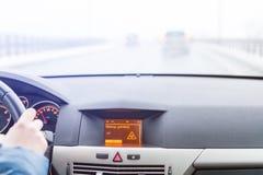 Advertencia resbaladiza del camino en la exhibición del coche, fuera del coche del foco en el fondo Fotos de archivo libres de regalías