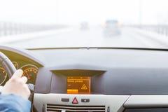 Advertencia resbaladiza del camino en la exhibición del coche, fuera del coche del foco en el fondo Foto de archivo libre de regalías