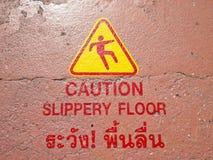 Advertencia resbaladiza en tailandés Foto de archivo libre de regalías