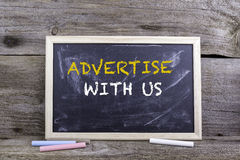 Advertise With Us. Chalk board on a wooden table.  Royalty Free Stock Photos