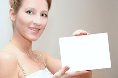 Advertisement. Smiling girl with white paper in the hands royalty free stock image