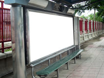 An advertisement board with bench underneath on the pavement. Bench at the bus stop beside the street with a blank advertisement board behind in Thailand stock photography