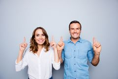 Advertisement concept. Portrait of caucasian, sweet, attractive, lovely, cute, funny, mature, adult couple pointing forefingers u royalty free stock photos
