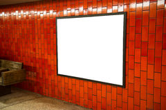 Advertisement empty poster space frame on the brick red wall on subway station Royalty Free Stock Image