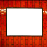Advertisement empty poster space frame on the brick red wall on subway station Stock Photos