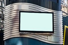Advertisement LCD TV Billboard. A LCD TV on a building for advertisement; used as a billboard; frame with black border; on a silver colored waved background Stock Images