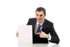Advertiser. Image of successful male pointing at blank paper and looking at camera with smile Stock Image