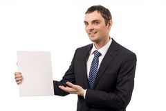 Advertiser. Image of successful male pointing at blank paper and looking at camera with smile Royalty Free Stock Image