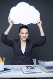 Advertiser. Portrait of young smiling female holding paper speech bubble and looking at camera Stock Image