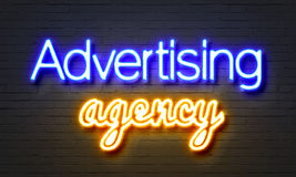Advertising agency neon sign on brick wall background. Stock Photo