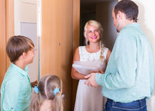 Advertising agent standing at doorway. Family with two kids welcoming advertising agent at doorway royalty free stock photography