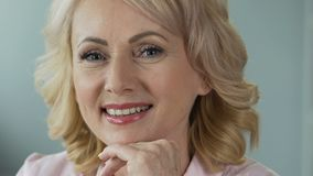 Advertising of anti-age cosmetics. Attractive mature woman smiling into camera