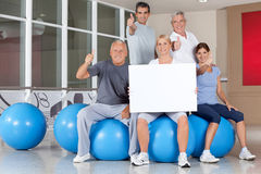 Advertising for back training. In gym with happy senior fitness group Stock Photos