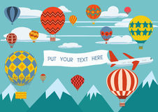 Advertising banners pulled by a plane with hot air balloons flying around Stock Image