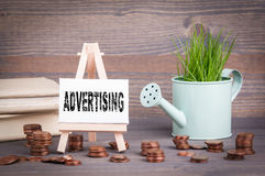 Advertising Business Concept. Miniature watering pot with fresh green spring grass and small change Stock Photography