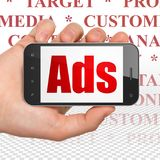Advertising concept: Hand Holding Smartphone with Ads on display. Advertising concept: Hand Holding Smartphone with red text Ads on display, Tag Cloud background stock photos