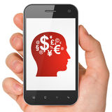 Advertising concept: Head With Finance Symbol on. Advertising concept: hand holding smartphone with Head With Finance Symbol on display. Mobile smart phone on Royalty Free Stock Images