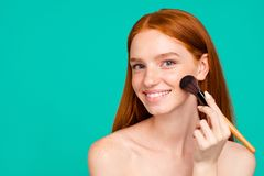 Advertising concept. Portrait of nice charming positive nude red-haired girl with shiny pure clean fresh smooth flawless. Skin with healthy tone, doing makeup royalty free stock photos
