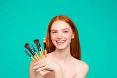 Advertising concept. Portrait of nice cheerful nude red-haired g. Irl with shiny pure clean fresh smooth flawless skin, demonstrating brushes for cool makeup stock photography