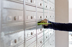 Advertising material in mailbox. Humand hand inserting advertising material in mailbox Royalty Free Stock Photography