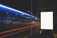 Advertising mock up banner on bus stop in night, public information board with blurred vehicles on high speed. Illuminated blank billboard with copy space for Stock Photography