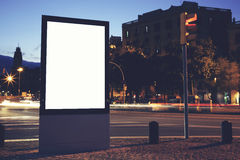 Advertising mock up banner in metropolitan city. Illuminated blank billboard with copy space for your text message or content, public information board in night Royalty Free Stock Images