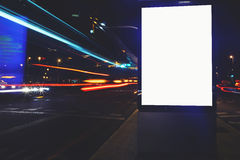 Advertising mock up in urban setting, empty poster on roadside. Illuminated blank billboard with copy space for your text message or content, public information royalty free stock image
