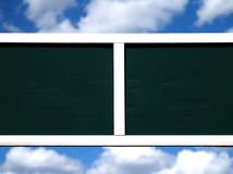 Advertising panel. A black advertising panel marked with white grids against a blue sky Stock Photos
