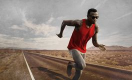 Advertising style portrait of young attractive and fit black African American runner man with athletic body doing running workout royalty free stock photography