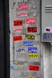 Colored farsi stickers on grey wall. Advertising in Teheran. Farsi characters on red, blue, yellow stickers glued on grey wall Royalty Free Stock Photos
