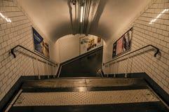 Advertizing och trappa i passagen som anknyter stationer av den Paris gångtunnelen Arkivfoton