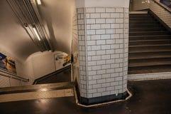 Advertizing och trappa i passagen som anknyter stationer av den Paris gångtunnelen Arkivbild