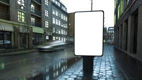 advertizingaffischtavla på stadsgatan på aftonen arkivbild