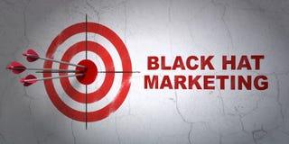 Advertizingbegrepp: marknadsföring för mål och för svart hatt på väggbakgrund Arkivbild