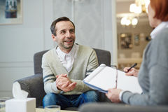 Advice of counselor. Happy men looking at his counselor and listening to her advice royalty free stock images