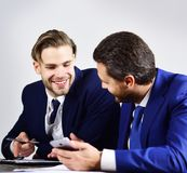 Advice from financial analyst. Businessman consults with expert. Business people with happy faces hold smartphone and notebook. Successful project, new stock photography
