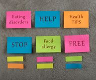 Advice of health concept - Many colorful sticky note with words eating disorders, help, health tips, stop, food allergy, free. On grey cement background. Copy stock photo