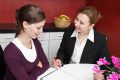 Advice at home. Customer service representative talking to a young woman Royalty Free Stock Photos