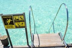 Advierta el reloj su muestra del paso cerca de las escaleras en el océano en Maldivas Imágenes de archivo libres de regalías