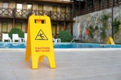 Advierta la muestra mojada del piso cerca de la piscina Imagen de archivo libre de regalías
