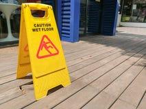 Advierta la señal de peligro mojada del piso con empañado en el piso de madera Foto de archivo libre de regalías