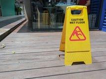 Advierta la señal de peligro mojada del piso con empañado en el piso de madera Fotografía de archivo libre de regalías