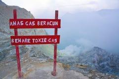 Advierta para guardarse del gas tóxico en el volcán de Kawah Ijen que arroga hacia fuera humo del azufre por la mañana Imágenes de archivo libres de regalías