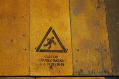 Advierta resbaladizo cuando peligros mojados señal adentro lengua china Imagen de archivo