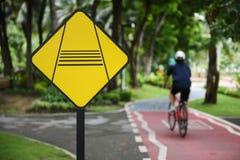 Advirta o sinal de tráfego do cavaleiro do slow down e bike pistas imagens de stock