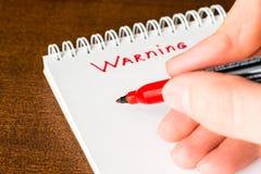 Advirtiendo, firme adentro el cuaderno del marcador rojo Foto de archivo libre de regalías