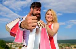 Adviseer hoogst verkoopuiteinden De mens met baard toont duim op gebaar Het paar in liefde adviseert het winkelen de zomerverkoop stock foto