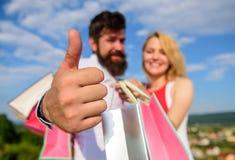 Adviseer hoogst verkoopuiteinden De mens met baard toont duim op gebaar Raadswinkel nu Het paar in liefde adviseert winkelend royalty-vrije stock foto's