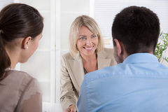 Adviser, broker and customers sitting at desk in the office. Royalty Free Stock Photography